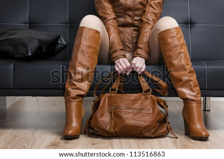 detail of sitting woman in brown clothes holding a handbag - stock photo