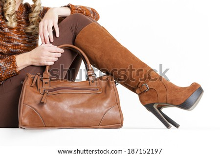 detail of sitting woman wearing brown clothes and boots with a handbag - stock photo