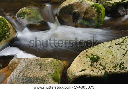 Detail of small beautiful cascade between mossy stones.  - stock photo