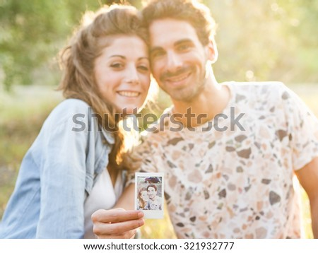 Detail of snapshot taken by a loving couple among the olive trees of a cultivated field in Tuscany during a picnic, Italy, in the background an old blue car. Man holding the instant photo - stock photo