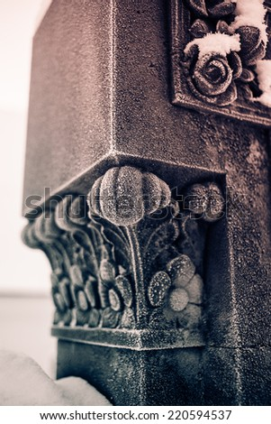 Detail of snow covered sculpture or pedestal of the grave in the cemetery of small town church. Atmospheric photo. Black and white photography. Sepia. Cream tone. - stock photo