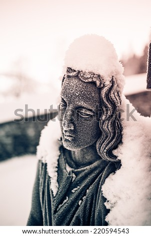 Detail of snow covered woman face of sculpture in the cemetery of small town church.  Atmospheric photo. Black and white photography. Sepia. Cream tone. - stock photo