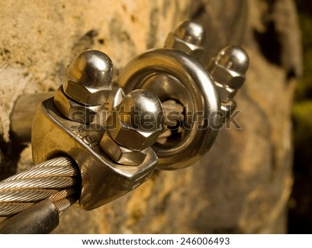 Detail of steel anchor eye and rope end anchored into sandstone rock. Iron twisted rope fixed in block by screws snap hooks.  - stock photo