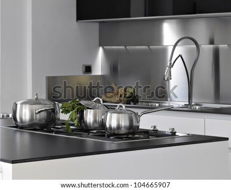 detail of steel saucepans with parsley in a modern kitchen - stock photo