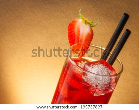 detail of strawberry cocktail with ice and space for text and golden gradient background - stock photo