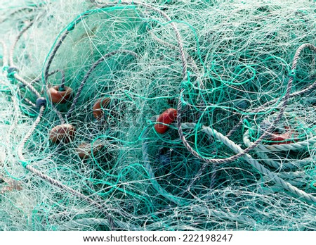 Detail of tangled green fishing nets  - stock photo