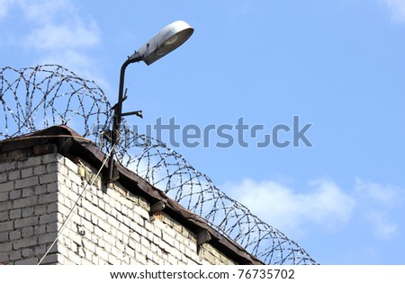 Detail of the brick prison wall with fence and lamp - stock photo