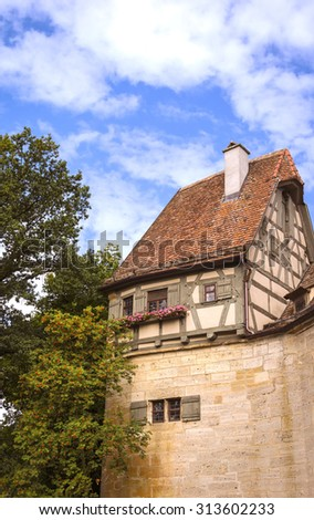 Detail of the city wall with a little small building at the top of the wall. This house is typical for the medieval city of Rothenburg ob der Tauber, Middle Franconia, Germany. - stock photo