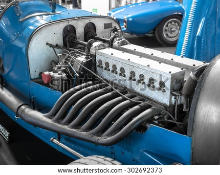 Detail of the engine and exhaust pipes of a blue vintage racing car. - stock photo