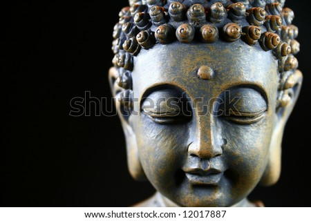 Detail of the face from buddha in front of black background - stock photo