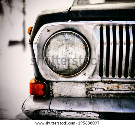 Detail of the front headlight of an old black car. This is dead car, black metal and chrome - stock photo