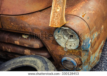 Detail of the front headlight of an rusty car in garage - stock photo