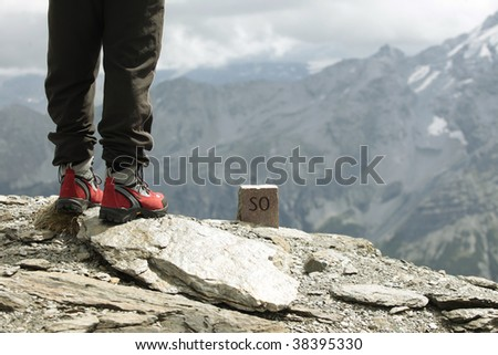 Detail of the legs of a walker at the top of a mountain in the Italian Alps - stock photo