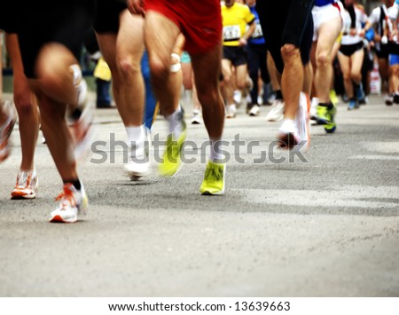 detail of the legs of runners at the start of a marathon race - stock photo