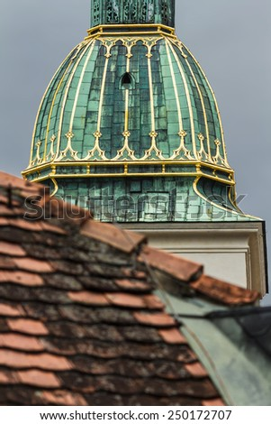 Detail of the main tower in Bratislava, Slovakia. Green roof with gold elements on a red tile roof - stock photo