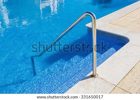 Detail of the steps of the pool. Handrails of metal. - stock photo