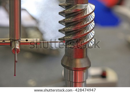Detail of the tip of a 3d laser scanner mechanical arm, with laser beam scanning a surface. - stock photo