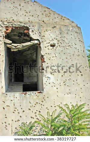 detail of the wall of a private home near Mostar in Bosnia where serbs attacked the house and murdered the occupants. - stock photo