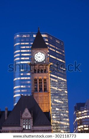 Detail of Toronto's city hall tower clock at dusk against modern building - stock photo