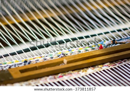 Detail of traditional weaving loom and thread. closeup on clothing craft tool. fashion wool on weaver. handmade fabric on loom. - stock photo