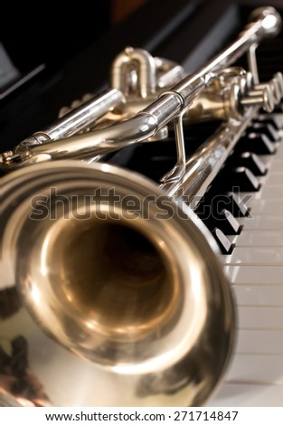 Detail of trumpet lying on the piano keys - stock photo