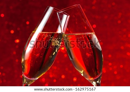 detail of two champagne flutes make cheers on red light bokeh background - stock photo