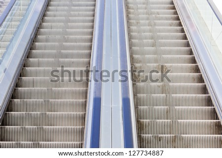 Detail of two empty symmetric moving stairs - stock photo