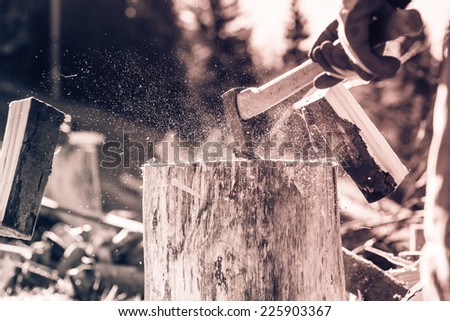 Detail of two flying pieces of wood on log with sawdust. Man is chopping wood with vintage axe. Frozen moment. Black and white photography. Sepia. Cream tone. - stock photo