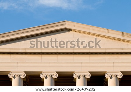 Detail of tympanum and columns of neoclassical building - stock photo
