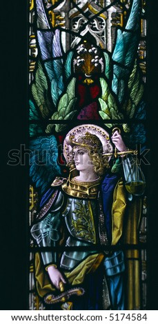 detail of victorian stained glass church window in Fringford depicting a typical victorian angel with a sword in his hands - stock photo