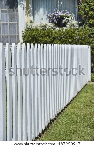 Detail of white picket fence next to lawn in front of house - stock photo