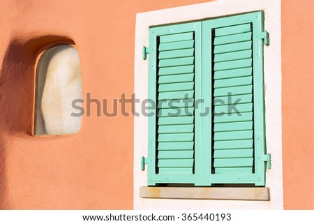 Detail of Window - Liguria Italy / Detail of a closed window with green shutter on orange wall - Liguria, Italy - stock photo