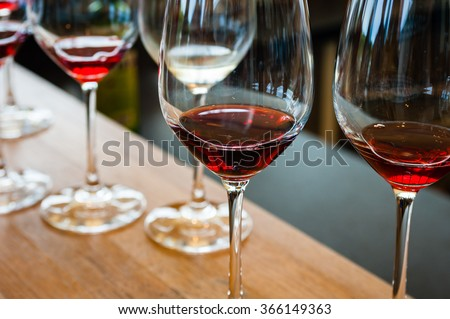 Detail of wine glasses with red wine samples, on wood counter with other glasses in background. - stock photo