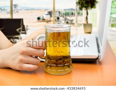 detail of woman drinking beer while working at the airport lounge - stock photo