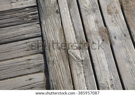 Detail of wooden boardwalk with sand at the beach - stock photo
