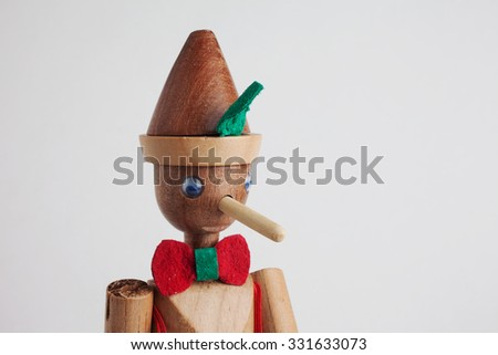 Detail of wooden doll of Pinocchio liar with big nose on white background  - stock photo