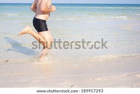 Detail of young man running at paradise beach in Phu quoc island, south of vietnam - stock photo