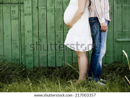 Detail of young pregnant couple in front of green fence in nature - stock photo