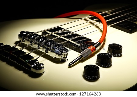 Detail on an electrical guitar and a red cord - stock photo