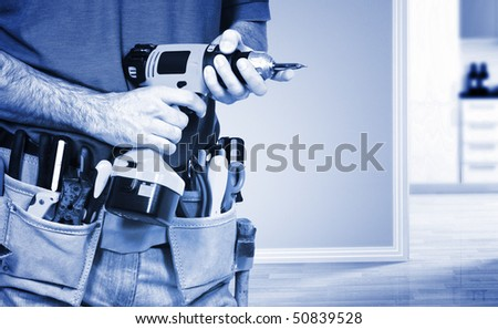 detail on handyman manual worker, toolsbelt and  drill in his hands - stock photo