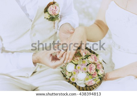 detail shot as the groom his bride the wedding ring on the finger pushes - stock photo