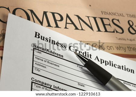 Detail shot of a business credit application with a pen and news paper. - stock photo