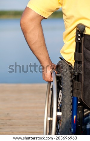 Detail shot of a man operating wheelchair  - stock photo