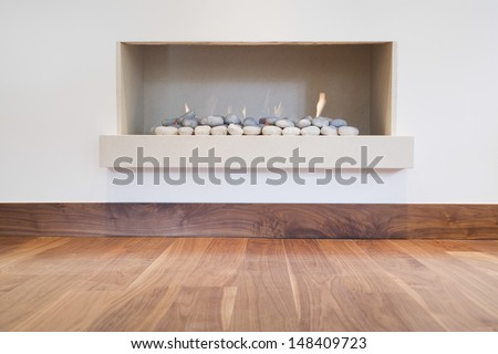 Detail shot of a modern simple fireplace with hardwood floor - stock photo