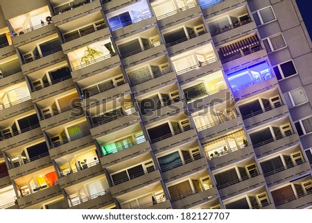 Detail shot of a tall illuminated apartment building at Europaplatz in Aachen, Germany at night  - stock photo