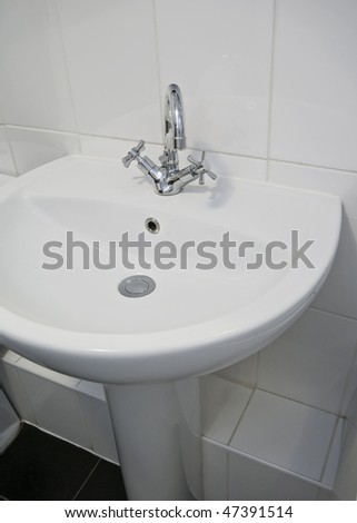 detail shot of a white ceramic hand wash basin with chrome tap - stock photo