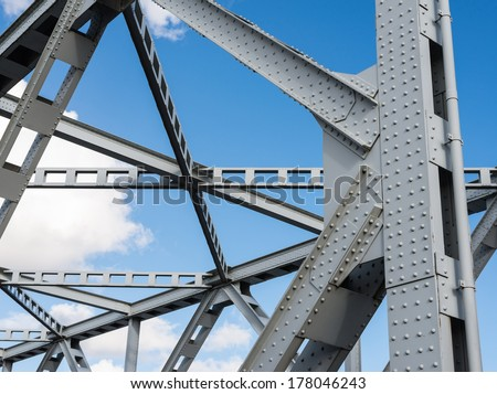 Detail shot of an historic gray painted Dutch riveted truss bridge against a blue sky. - stock photo