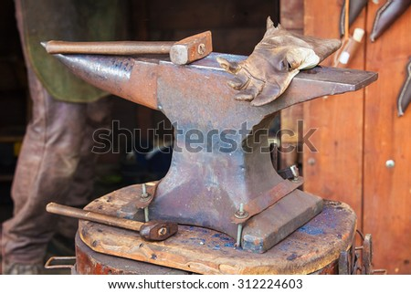Detail shot of hammer on blacksmith anvil - stock photo