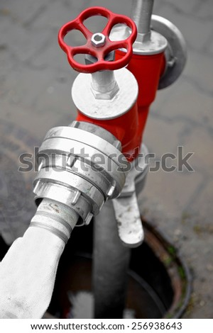 Detail shot with a white hose connected to a red hydrant - stock photo