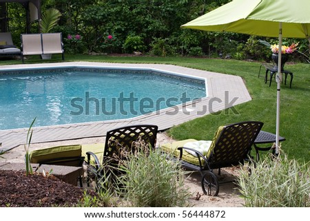 Detail view of a luxurious in ground pool and patio lounge.  This partly wooded backyard garden offers the same level of luxury found in many vacation resorts. - stock photo
